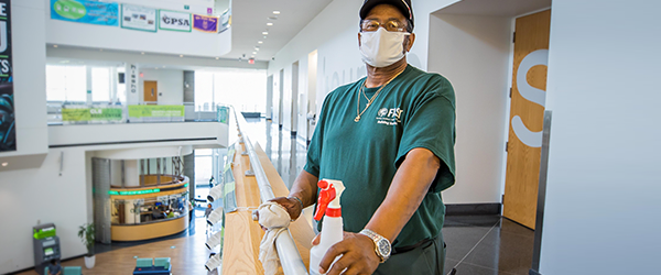 Cleveland State University facilities team member with cleaning supplies