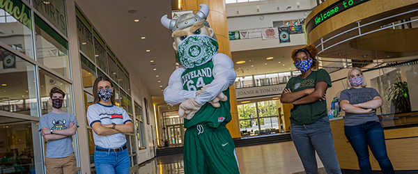 Magnus standing with Cleveland State University students wearing masks