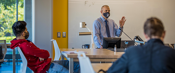 Cleveland State University professor wearing a mask addresses class