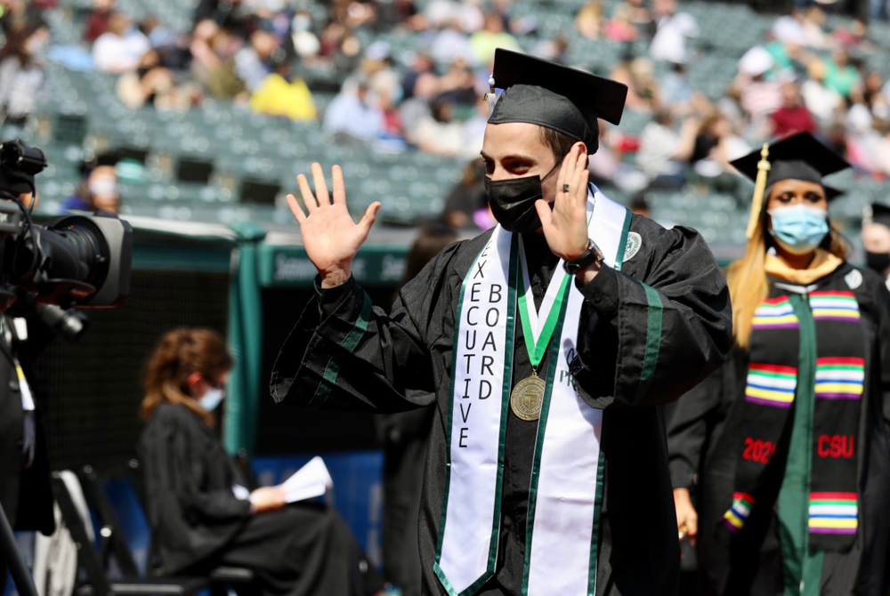 Student waving at Spring 2021 Commencement