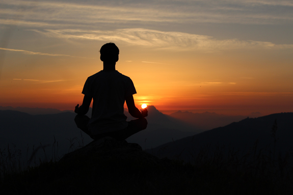 man meditating on a hill at sunset