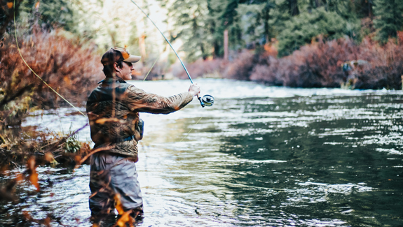 man fly fishing in river