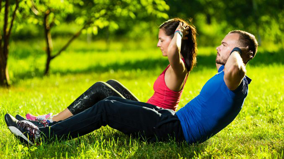 couple doing sit-ups in park