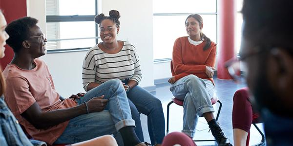 A diverse group of students sitting in a circle, smiling while in group therapy.