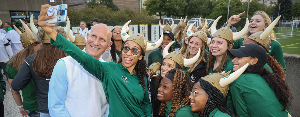 CSU President Sands with group of students at Homecoming
