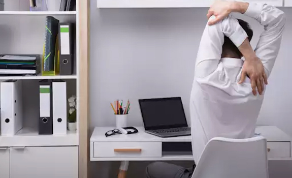 man working at home stretching at desk
